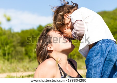 young happy mother playing with her child girl outdoors #199804280