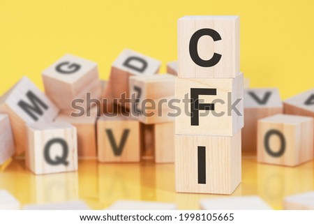 wooden cubes with letters CFI arranged in a vertical pyramid, yellow background, reflection from the surface of the table, business concept. cfi - short for custom factory integration