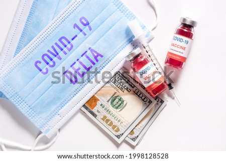 Top view of new coronavirus infection vaccine against COVID-19 Delta variant strain with dollar bills and clean medical mask on white background