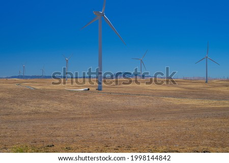 Windustry, an airfoil lays on the ground afoot of a wind turbine on the wind farm. Royalty-Free Stock Photo #1998144842