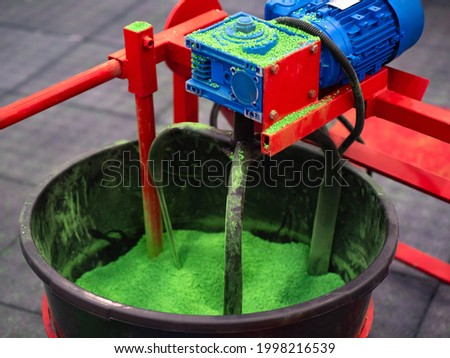 Blade mixer for rubber crumb. Grinding green caoutchouc crumb. Mixing of rubber raw materials. Blade mixer while working. Production of rubber tiles concept. Recycling of caoutchouc process. Royalty-Free Stock Photo #1998216539