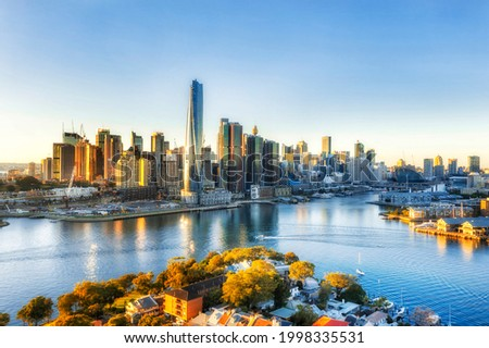 Sunrise over City of Sydney CBD high-rise towers around Darling Harbour - aerial view from Inner City suburbs. Royalty-Free Stock Photo #1998335531