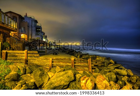 Houses on the coast in the late evening. Coastal houses in evening. Evening light at coasline. Coasline evening panorama Royalty-Free Stock Photo #1998336413