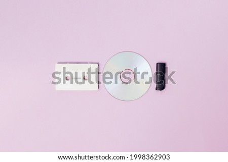 White radio cassette for cassette player and cd and black usb flash memory on a purple background