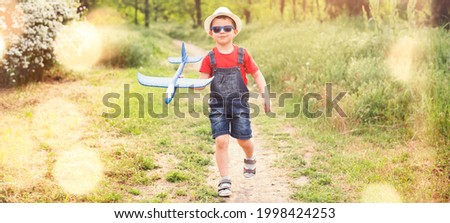 Cute baby boy walking in the park with a foam blue airplane in denim overalls shorts, blue sunglasses and a white hat. Wide photo.
