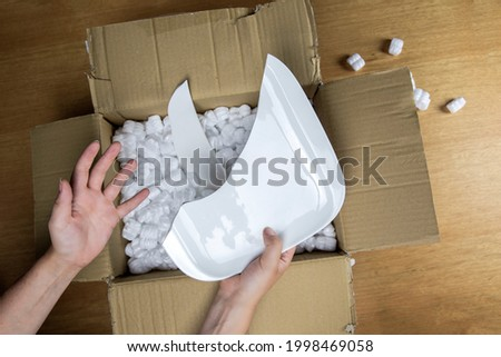 Broken plate in damaged cardboard box top view, damaged home delivery unpacking box close up Royalty-Free Stock Photo #1998469058