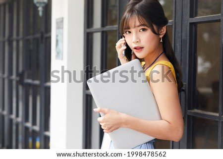 A young asian business woman, beautiful female model is calling with her smartphone while holding a laptop at the office with yellow cloth looking pretty Royalty-Free Stock Photo #1998478562