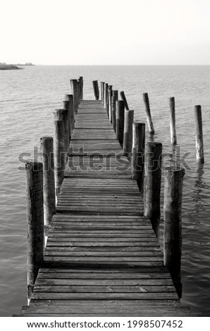 By the sea, beautiful view of a wooden pier, black and white photography. Wooden pier leading to the sea ocean or lake,boardwalk. Neusiedler See, Burgenland, Austria. Royalty-Free Stock Photo #1998507452