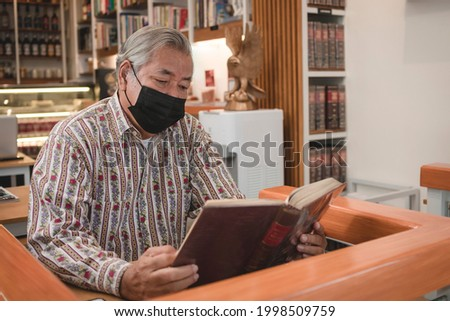 An old Filipino man in a face mask reviews a law book at a bookstore cafe. Casual reading at a Hybrid establishment. Royalty-Free Stock Photo #1998509759