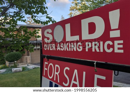 New sign sold over asking price for sale in front of detached house in residential area. Real estate bubble, crash, hot housing market, overpriced property, buyer activity concept. Selective focus.