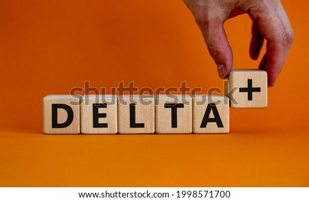 Covid-19 delta plus variant symbol. Doctor holds the wooden cube and changes words Delta to Delta plus. Beautiful orange background. Copy space. COVID-19 new delta plus variant concept.
