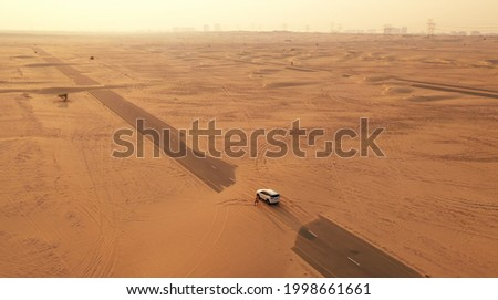 Back view blond hair woman with yellow authentic backpack looking on sandy road after sandstorm. Travel adventures in desert. Royalty-Free Stock Photo #1998661661