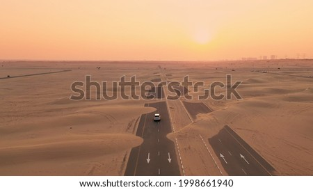 Back view blond hair woman with yellow authentic backpack looking on sandy road after sandstorm. Travel adventures in desert. Royalty-Free Stock Photo #1998661940