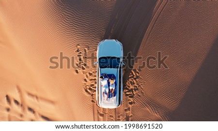 AERIAL. Top view of young couple relaxing on the car's roof at the desert. Royalty-Free Stock Photo #1998691520