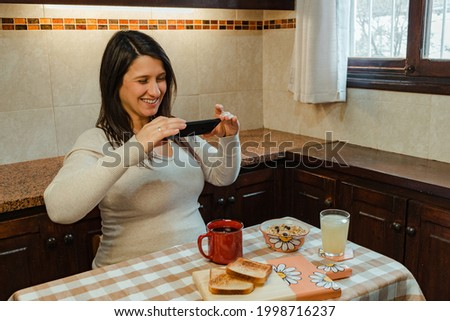 Pregnant Hispanic woman taking a picture of her breakfast. Concept of good health during pregnancy and technology. Copy space.