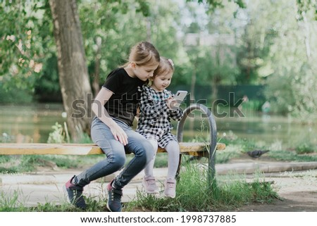 Two sisters sitting on bench in spring summer park and watching cartoons on smartphone. Wireless technologies concept. Children addiction from gadgets.