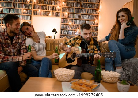 Young group of friends on a house party playing guitar and having fun while drinking beer and eating snacks