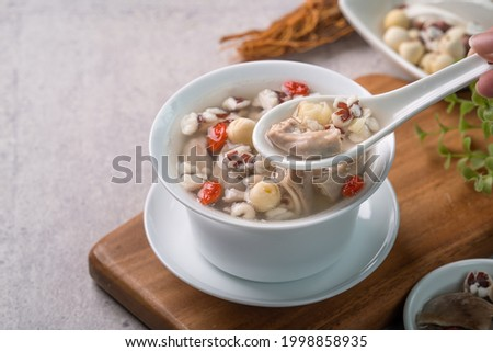 Four Tonics Soup. Close up of delicious homemade Taiwanese traditional Chinese herb flavor food with herbs, pork intestine on gray table background Royalty-Free Stock Photo #1998858935