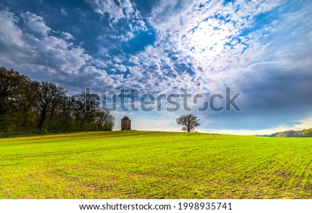 Cloudy sky over a green agriculture meadow. Agriculture field above cloudy sky. Cloudy sky over agriculture field Royalty-Free Stock Photo #1998935741