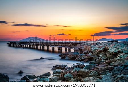 Lake pier on the background of sunset. Sunset lake pier landscape. Lake pier at sunset. Beautiful sunset on lake pier Royalty-Free Stock Photo #1998935771