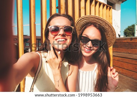 Two young beautiful smiling hipster female in trendy summer clothes.Sexy carefree women posing on the street background in hat. Positive pure models having fun at sunset, taking Pov selfie Royalty-Free Stock Photo #1998953663