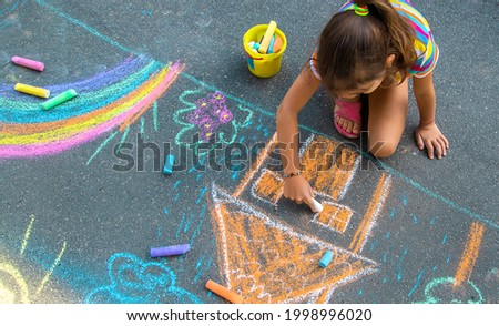The child draws a house and a rainbow on the asphalt with chalk. Selective focus. Kids. Royalty-Free Stock Photo #1998996020