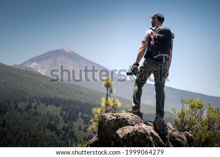 A photographer observes the horizon with his camera in hand from the top of a mountain. You see the landscape with forests, mountains and a volcano. Travel or adventure concept.
