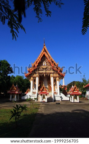picture of a church in a Thai temple with the morning sun and dark blue sky. There are trees in the foreground and shadows of trees