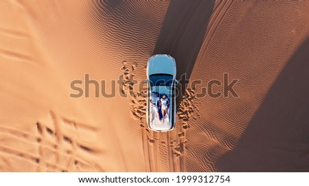 AERIAL. Top view of young couple relaxing on the car's roof at the desert. Royalty-Free Stock Photo #1999312754