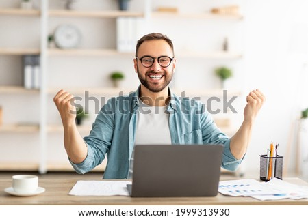 Young guy making YES gesture in front of laptop at home office. Millennial man reaching success, working with portable pc, making profitable deal, signing online contract, celebrating achievement