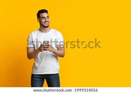 Cheerful arab guy with smartphone looking at copy space and smiling, yellow studio background, panorama. Positive middle-eastern young man chatting on mobile phone, using new application Royalty-Free Stock Photo #1999314056