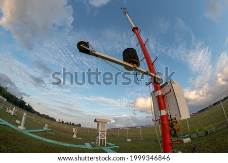 An Automatic Weather Station at Bali Meteorology Station with a landscape of Meteorological garden in the morning. Under the blue sky with partly grey cumulus and cirrus clouds. Shoot on fisheye lens Royalty-Free Stock Photo #1999346846