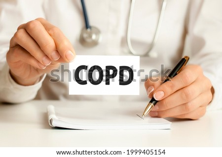 COPD card in hands of medical Doctor. Doctor's hands a sheet of paper with text COPD, medical concept. COPD - short for chronic obstructive pulmonary disease Royalty-Free Stock Photo #1999405154