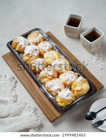 Kue soes original, soes original or cream puffs or Choux Pastry Cream Puffs, pastry ball filled with whipped cream, crispy and airy choux pastry shells are filled with smooth and soft cream. Royalty-Free Stock Photo #1999481465