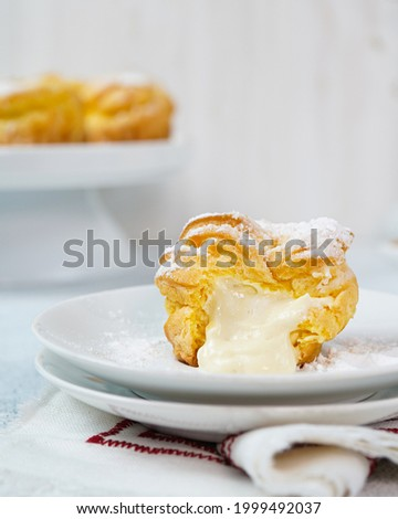 Melted cream,kue soes original,soes original or cream puffs or Choux Pastry Cream Puffs,pastry ball filled with whipped cream, crispy and airy choux pastry shells are filled with smooth and soft cream Royalty-Free Stock Photo #1999492037