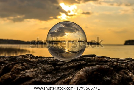 Sunset view over the lake through a glass ball. Transparent sphere on lake at sunset. Lake at sunset in clear sphere. Lake at sunset in glassware ball Royalty-Free Stock Photo #1999565771