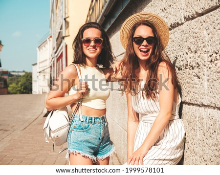 Two young beautiful smiling hipster female in trendy summer clothes.Sexy carefree women posing in the street near wall in hat. Positive pure models having fun at sunset, hugging  Royalty-Free Stock Photo #1999578101