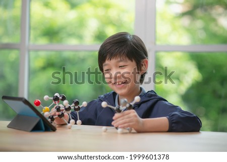 Asian child with hearing aid constructing molecular model  in science classroom online at home
