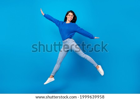 Full length body size side profile photo young woman jumping up careless isolated vibrant blue color background Royalty-Free Stock Photo #1999639958