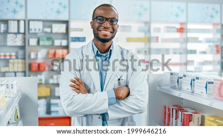 Pharmacy: Professional Confident Black Pharmacist Wearing Lab Coat and Glasses, Crosses Arms and Looks at Camera Smiling Charmingly. Druggist in Drugstore Store with Shelves Health Care Products Royalty-Free Stock Photo #1999646216