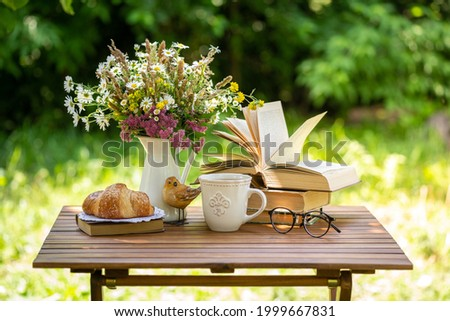 Bouquet of meadow flowers, croissant, cup of tea or coffee, books on table in summer idyllic garden. Rest in garden, reading books, breakfast, vacations in nature concept. Summertime in garden Royalty-Free Stock Photo #1999667831