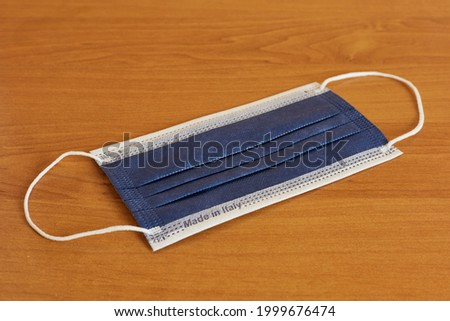Blue colored surgical facial mask made in Italy. To prevent the spread of COVID-19. New and placed on an orange wooden table and uniformly illuminated. Healthcare, personal protection device, DPI