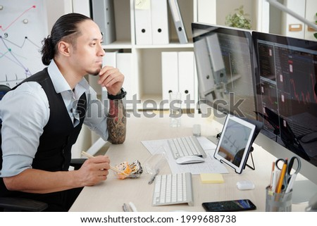 Pensive trader eating rolls when analyzing stock market trends on computer screen in front of him, thinking what stocks and futures to buy and sell