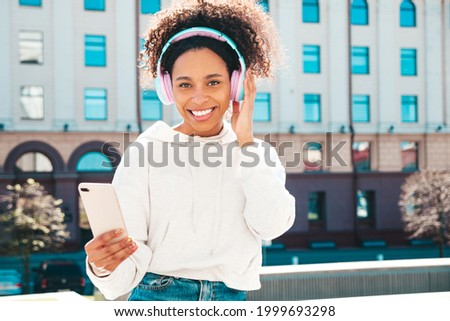 Beautiful black woman with afro curls hairstyle.Smiling model in white hoodie.Sexy carefree female enjoying listening music in wireless headphones.Posing on street background at sunset.Holds phone