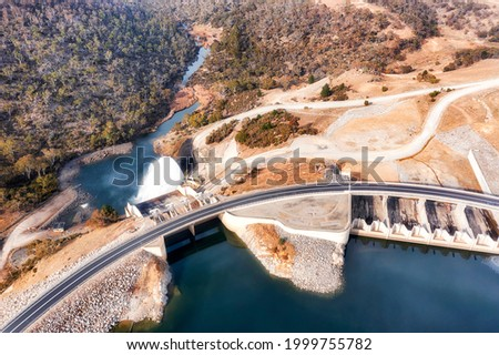 Power generation dam on Snowy River in Snowy mountains of Australia - Lake Jindabyne. Aerial top down view over gate and spillway. Royalty-Free Stock Photo #1999755782