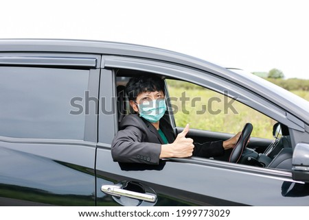 A man wearing a work suit drives a sedan to work in the city. wearing a medical mask to prevent infection during the coronavirus epidemic The driver of the sedan wears a mask for Covid-19. Royalty-Free Stock Photo #1999773029