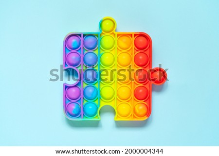 Colorful rainbow trendy Pop it fidget toy on blue background