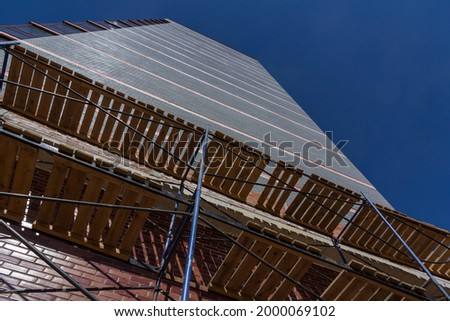 Scaffolding on the background of the building facade. Building construction