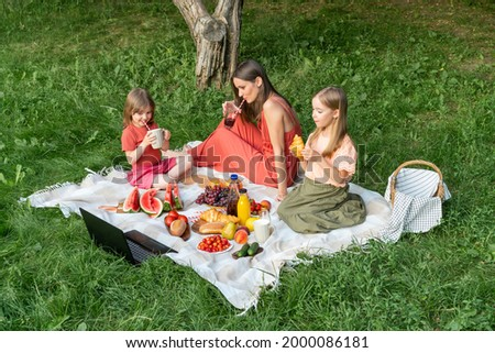 Young mother with two little daughters on picnic in evening summer park, drinking juice while sitting on blanket, eating healthy food, watching cartoons on laptop.