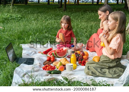 Young mother with two little daughters on picnic in evening summer park, sitting on blanket, watching cartoons on laptop.